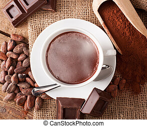 Cup of hot chocolate with cocoa powder, cocoa beans and...