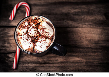 Cup of hot chocolate with marshmallows and candy cane on a...
