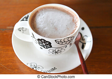 Cup of hot cocoa with wooden spoon