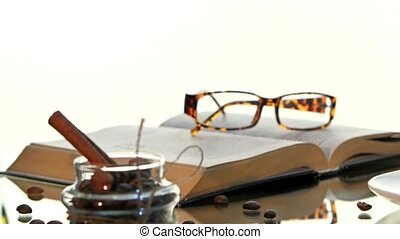 Cup of hot coffee and book with glasses, cinnamon, beans on white background