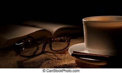 Cup of hot coffee and book with glasses, cinnamon on black background, cam moves to the right