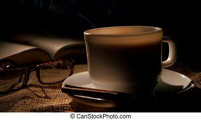Cup of hot coffee and book with glasses, cinnamon on sacking, black background