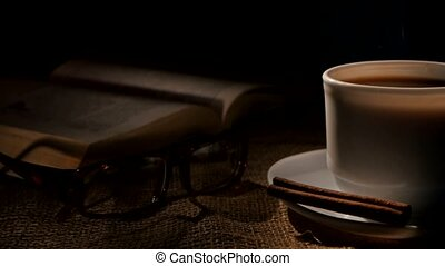 Cup of hot coffee and book with glasses, cinnamon on sacking, black background, cam moves to the right