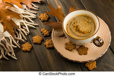 Cup of hot coffee cookies plaid with oak leaves on wooden background