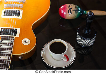 Cup of hot coffee in music on black background