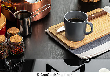Cup of hot coffee on wooden board on kitchen table
