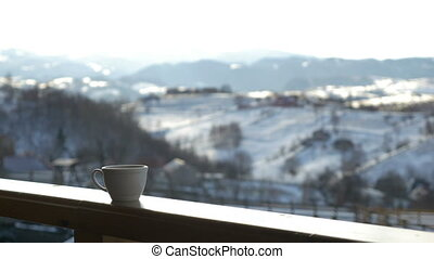 Cup of hot coffee on wooden railing