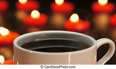 Cup of hot coffee with a burning candle. Closeup