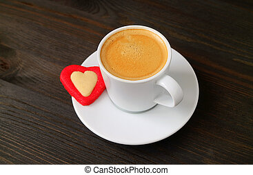 Cup of Hot Coffee with a Heart Shaped Cookie on Dark Brown Wooden Background for Valentine's Day Concept
