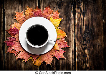 Cup of hot coffee with autumn leaves.