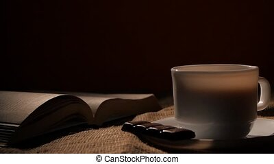 Cup of hot coffee with chocolate and open turning pages book on black background