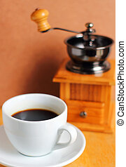 Cup of hot coffee with coffee grinder and beans