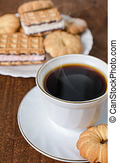 Cup of hot coffee with pastry. Dark wooden background.
