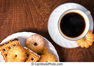 Cup of hot coffee with pastry on dark wooden board. Top view.