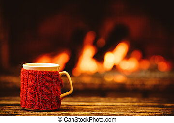 Cup of hot drink in front of warm fireplace. Holiday ...