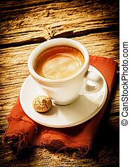 Cup of hot frothy espresso coffee served on a rustic cloth with a small macaroon in a rural country cafeteria on a weathered wood surface with vignetting and copyspace