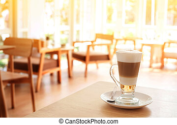 Cup of Hot Latte Coffee on wood table with light window.