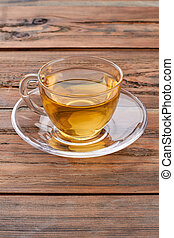 Cup of hot tea on brown wooden background.