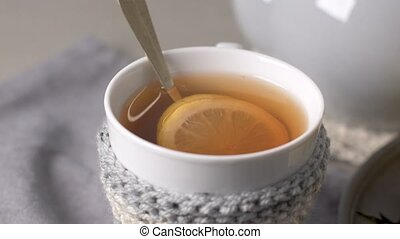 Cup of hot tea with lemon dressed in knitted warm winter...
