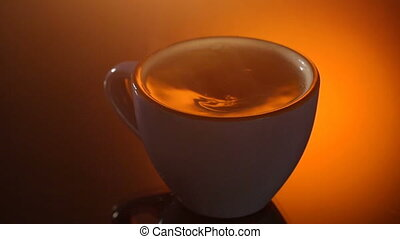 Cup of hot tea with steam on shiny background.