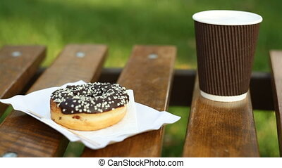 cup of latte and muffin on a park bench.