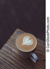 Cup of latte coffee on the wood table