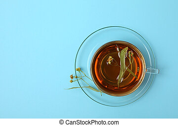 Cup of linden tea on blue background, top view