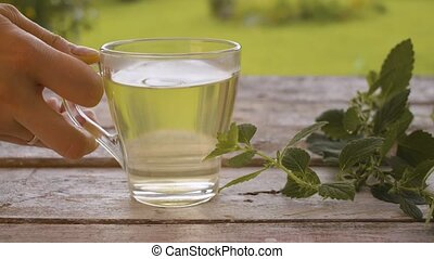 Cup of melissa drink - Close-up hand placing down a ...