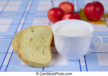Cup of milk with a cornbread and apples