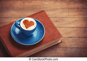 Cup of ?offee with shape heart and book on a wooden table.