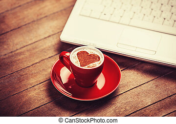 Cup of ?offee with shape heart and laptop on a wooden table.