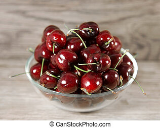 Cup of ripe cherries on a wooden background