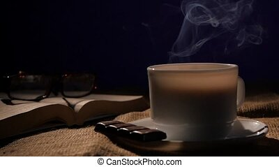 Cup of smoking coffee with chocolate, glasses and open book on black background