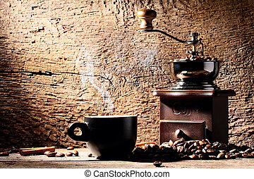 Cup of steaming coffee on background coffee grinders