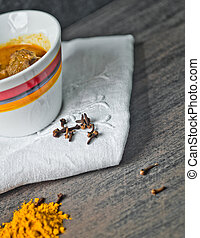 cup of steaming hot soup with spices on raw cotton embroidered tablecloth