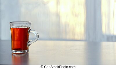 Cup of steaming hot tea on the table against the window.