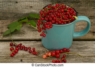 Cup of sweet red currants on a dark rustic wooden table