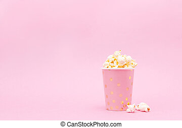 cup of tasty popcorn on a pink background