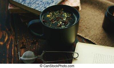Cup of tea among books - Black mug with fresh tea leaves on...