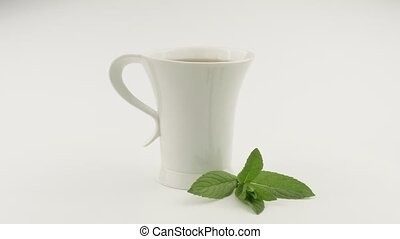 Cup of tea and a green sprig of mint. White background. ...