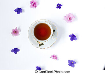 cup of tea and branch of small pink and lilac flower on white background