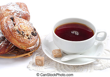 Cup of tea and buns with raisins