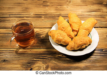 Cup of tea and croissants on wooden table