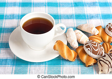 Cup of tea and delicious cookies on blue checkered tablecloth