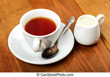 Cup of tea and jug with milk on a wooden table