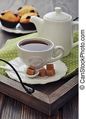Cup of tea and teapot on wooden tray closeup