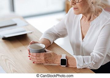 Cup of tea being held by a professional businesswoman