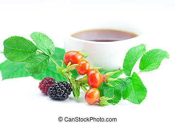 cup of tea, blackberry, raspberry and rosehip berries with leaves