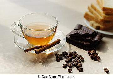 Cup of tea, coffee beans, cinnamon sticks, anise and chocolate