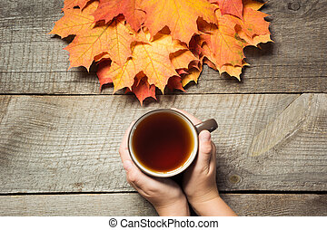 Cup of tea in hand, autumn leaves on wooden board. Fall still life, vintage style. Top view.